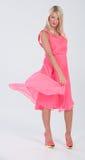 Blondes behaartes Modell im gekräuselten rosa Kleid Stockfoto