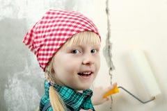 Blondes blauäugiges kleines Mädchen, das Reparaturen in der Wohnung tut Stockbilder
