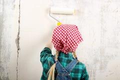 Blondes blauäugiges kleines Mädchen, das Reparaturen in der Wohnung tut Stockfotos