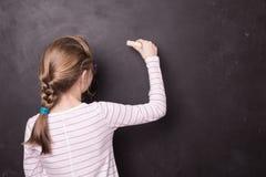 Blondes chid Mädchen-Kinderschreiben auf Schultafel Lizenzfreies Stockbild