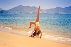 blondes dünnes Mädchen in den Bikinihaltungen in Armstandposition auf Strand Lizenzfreies Stockfoto