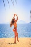 Blondes dünnes Mädchen in den Bikinihaltungen auf Sandwind rüttelt langes Haar Stockfotos