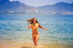 Blondes dünnes Mädchen in den Bikinihaltungen im seichten Meerwasser lächelt Lizenzfreie Stockfotos