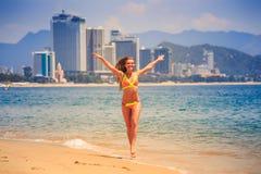 Blondes dünnes Mädchen in den Bikinihaltungen lächelt auf Rand von azurblauem Meer Lizenzfreies Stockfoto