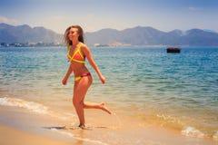 blondes dünnes Mädchen in den Bikiniläufen aus dem Meer heraus, zum des Lachens auf den Strand zu setzen Stockfoto