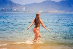 blondes dünnes Mädchen in den Bikiniläufen in Meer spritzt gegen Hügel Stockfoto
