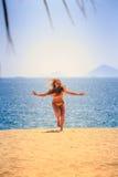 blondes dünnes Mädchen in den Bikiniläufen vom Meer auf Sand lacht Lizenzfreies Stockbild
