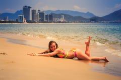 Blondes dünnes Mädchen in den Bikinilügen auf Magen lächelt auf nassem Sand Lizenzfreie Stockfotos