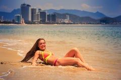blondes dünnes Mädchen in den Bikinilügen unterstützen an im Rand des Seelächelns Lizenzfreie Stockbilder