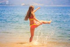 Blondes dünnes Mädchen in den Bikinischritten in Meer spritzt auf Strand Lizenzfreies Stockfoto