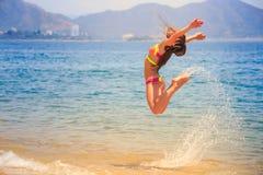 Blondes dünnes Mädchen im Bikini im Sprung über Meer spritzt Lizenzfreie Stockbilder