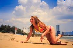 blondes dünnes Mädchen im Bikini kriecht eine Hand oben entlang nassem Sand Stockbilder