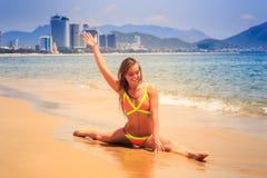 Blondes dünnes Mädchen im Bikini macht Spalte auf nassem Sandlächeln in Meer Lizenzfreie Stockfotos