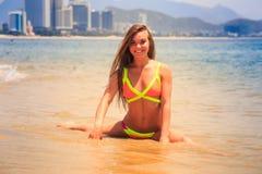Blondes dünnes Mädchen im Bikini macht Spalte auf nassem Sandlächeln in Meer Stockfotos