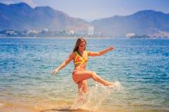 Blondes dünnes Mädchen im Bikini macht spritzt im Meer gegen Hügel Lizenzfreie Stockfotografie