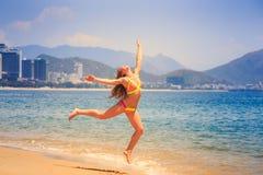 blondes dünnes Mädchen im Bikini springt auf Strand Lizenzfreies Stockfoto