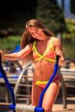 Blondes dünnes Mädchen im Bikini steht auf Simulator gegen Anlagen Lizenzfreie Stockfotografie