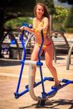 Blondes dünnes Mädchen im Bikini steht auf Simulator gegen Anlagen Lizenzfreie Stockbilder