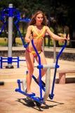 Blondes dünnes Mädchen im Bikini steht auf Stepper auf Sportplatz Lizenzfreies Stockfoto