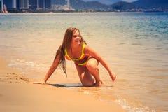 Blondes dünnes Mädchen im Bikini zieht auf Handknie aus Wasser heraus um Stockfotografie