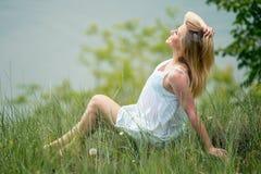 Blondes dünnes Mädchen im weißen Kleid, aufwerfend auf Gras an der Wiese Stockbilder