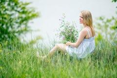 Blondes dünnes Mädchen im weißen Kleid sitzt auf dem Gras und hält bouq Stockbild
