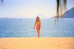 blondes dünnes Mädchen in den Bikiniwegen vom azurblauen Meer auf Sand lächelt Stockfoto