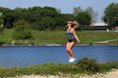 Blondes Eignungsmädchenseil, das in einem Fluss springt Stockbild
