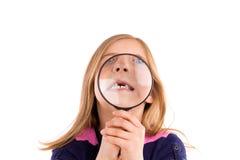 Blondes eingedrücktes Mädchen mit den Zähnen in der Lupe Lizenzfreie Stockfotografie