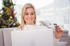 Blondes Einkaufen online auf der Couch am Weihnachten Lizenzfreie Stockbilder