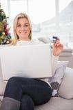 Blondes Einkaufen online auf der Couch am Weihnachten Stockfotografie