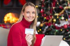 Blondes Einkaufen online mit Laptop am Weihnachten Lizenzfreie Stockbilder