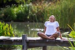 Blondes entspannendes Mädchen des Zens 20s, Teichumwelt Stockfoto