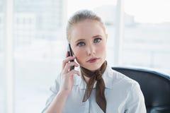 Blondes ernstes Geschäftsfrauanrufen Stockfotos