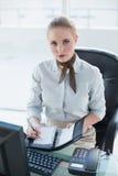 Blondes ernstes Geschäftsfrauschreiben im Tagebuch Stockfotografie