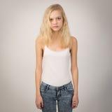 Blondes ernstes Mädchen, das gerade steht, tragend eine weiße Spitze Stockfoto