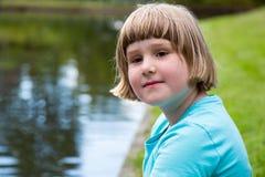 Blondes europäisches Mädchen, das in Teich sitzt Lizenzfreie Stockbilder