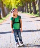 Blondes Forscherkindermädchen, das mit Rucksack in den Herbstbäumen geht Stockfotos