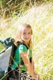Blondes Forscherkindermädchen, das mit Rucksack im Gras geht Stockbild