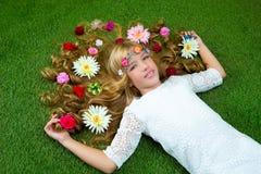 Blondes Frühlingsmädchen mit Blumen auf Haar über Gras Lizenzfreies Stockfoto