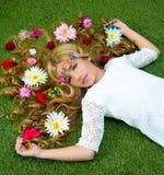 Blondes Frühlingsmädchen mit Blumen auf Haar über Gras Stockfotografie