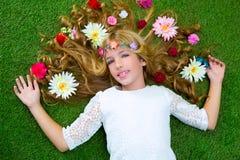 Blondes Frühlingsmädchen mit Blumen auf Haar über Gras Lizenzfreie Stockfotos