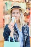 Blondes Fraueneinkaufen mit Kreditkarte Stockfoto