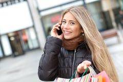 Blondes Fraueneinkaufen und -c$anrufen Lizenzfreie Stockfotos