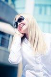Blondes Frauengespräch durch das Telefon im Freien Stockbild