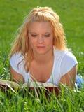 Blondes Frauenlesebuch draußen Stockfotos