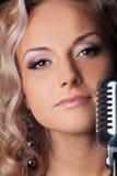 Blondes Frauenportrait der Schönheit mit Mikrofon Stockfoto