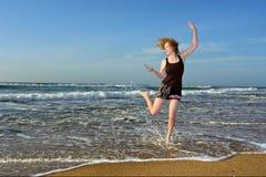 Blondes Frauentanzen mit Handy auf Strand Stockbilder