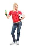 Blondes Gebläse, das eine Flasche und einen Fußball anhält Lizenzfreies Stockfoto