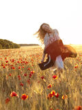 Blondes Gehen auf dem Mohnblumegebiet Stockfotos